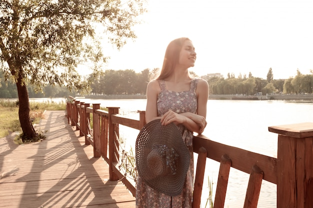 Girl in dress with long hair posing near water. summer portrait of girl at sunset.