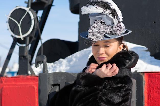 증기 기관차 근처에서 19세기 귀족 여성으로 분장한 소녀. 러시아 겨울