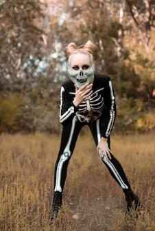 秋の森で骸骨に扮した少女。彼女はひどく立って、カメラを見つめていました。ハロウィーン