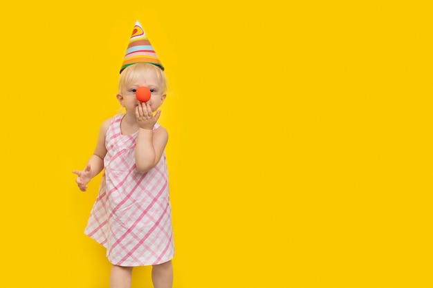 Girl dressed as clown with party hat sends kiss