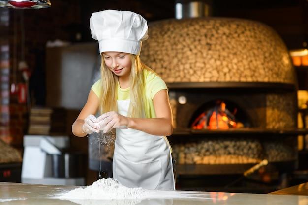 Девушка в костюме повара, замешивающего тесто