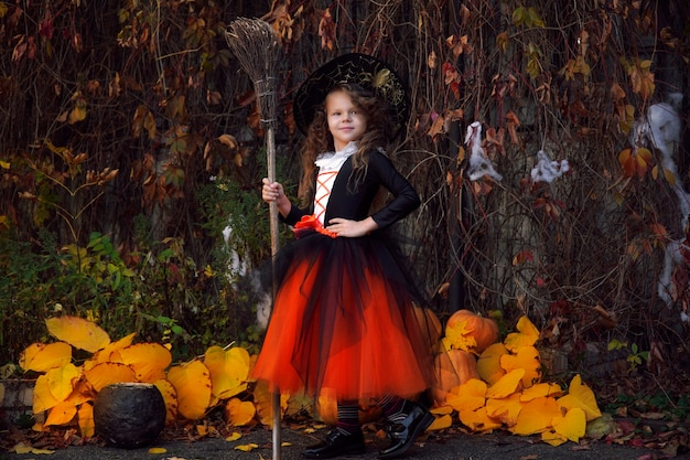 A girl dressed as a little witch in an orange puffy skirt and a pointed black hat with a broom near halloween pumpkins in an autumn park in the afternoon