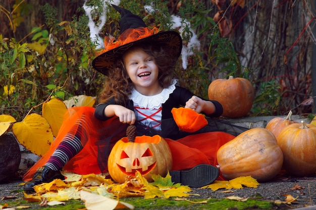 A girl dressed as a little witch in an orange skirt and a pointed black hat sits next to halloween pumpkins in an autumn park