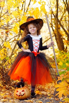 A girl dressed as a little witch in an orange skirt and a pointed black hat with a broom in an autumn halloween park with a pumpkin