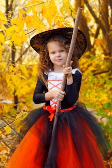 A girl dressed as a little witch in an orange skirt and a pointed black hat with a broom in an autumn halloween park
