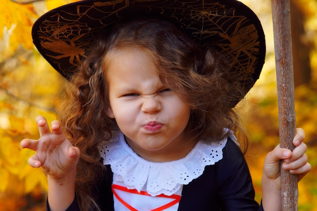 A girl dressed as a little witch in a pointed black hat frowns in an autumn halloween park
