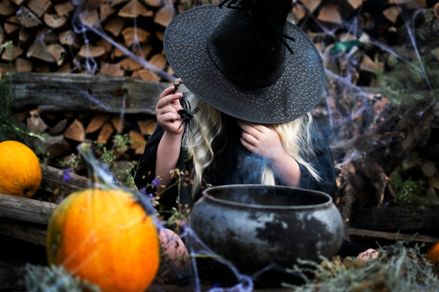 Girl dressed as a witch, black hat, long white hair, black spider, halloween holiday