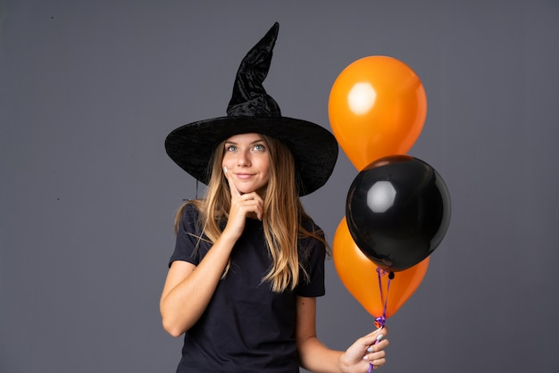 Girl dressed as a witch for halloween and having doubts