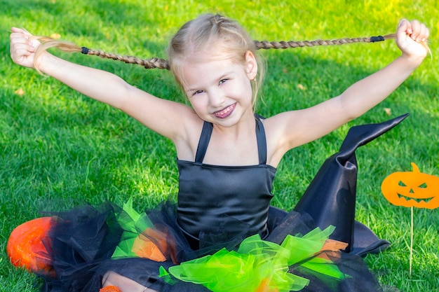 Girl dressed as a witch for the holiday of halloween. happy girl holding her pigtails