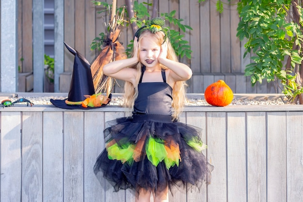 Girl dressed as a witch for the holiday of halloween. happy girl with a spider on her head