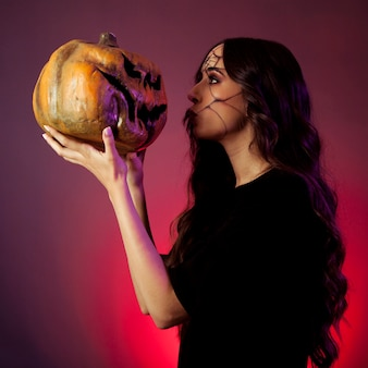 Girl dressed as witch looking at pumpkin