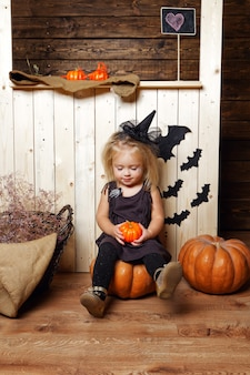 A girl dressed as a witch with halloween decorations