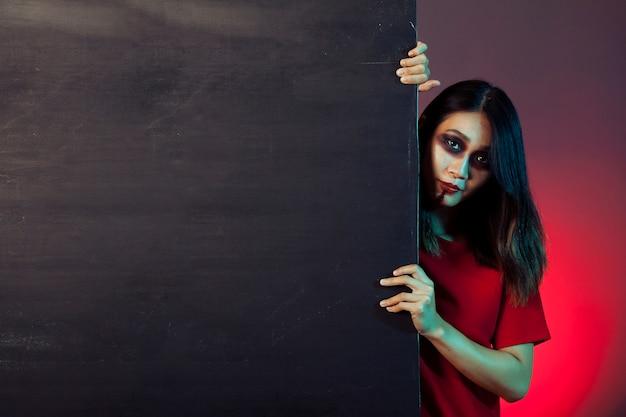 Girl dressed as zombie behind wall