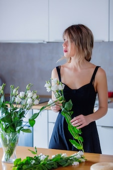 A girl dressed in a black dress is holding white roses in a bouquet before putting them in a vase. sprint time concept