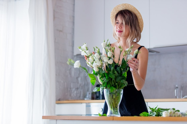 Girl dressed in a black dress near white roses bouquet in a vase