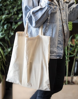 Ragazza vestita in giacca di jeans che tiene eco-borsa