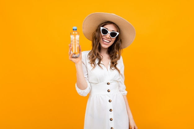 Girl dressed in a dress with sunglasses and a hat holds a bottle of water on a yellow banner background