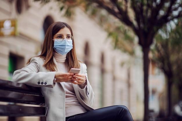 外のベンチに座ってスマートフォンを使用してフェイスマスクでファッショナブルな服を着た女の子。コロナウイルス中のミレニアル世代。