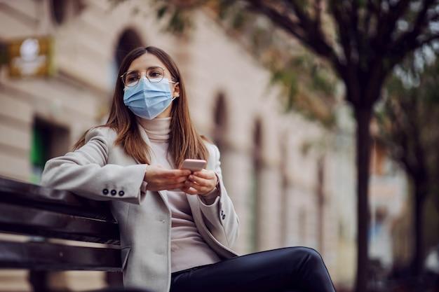 外のベンチに座ってスマートフォンを使用してフェイスマスクでファッショナブルな服を着た女の子。