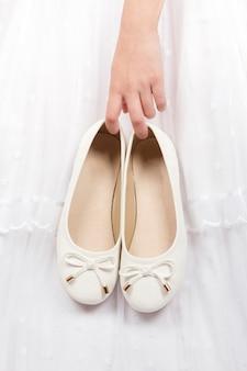 행사를 위해 옷을 입은 소녀는 그녀의 손에 그녀의 흰색 신발을 보유하고 있습니다.