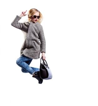 Girl dressed in grey fur coat, wearing sunglasses and black bag,