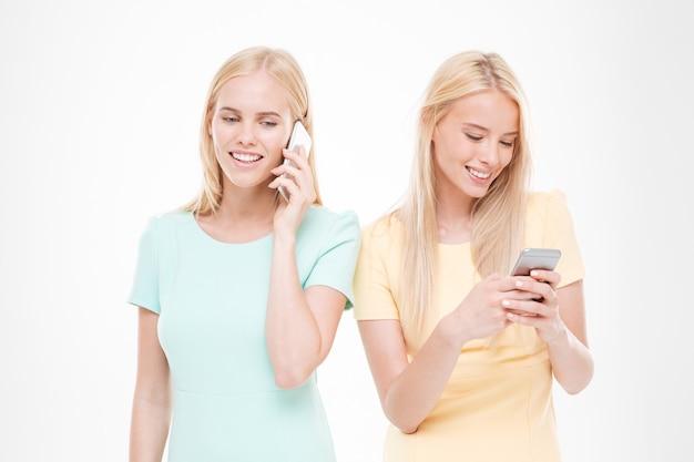 彼女の電話で話している青いドレスを着た女の子とチャットしている黄色のドレスを着た女性