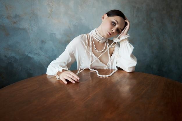 首に白い真珠のビーズが付いた白い自由奔放に生きる服を着た女の子がテーブルに座っています。完璧な笑顔、女性のロマンチックなセクシーなイメージ、きれいな滑らかな肌と美しいメイク