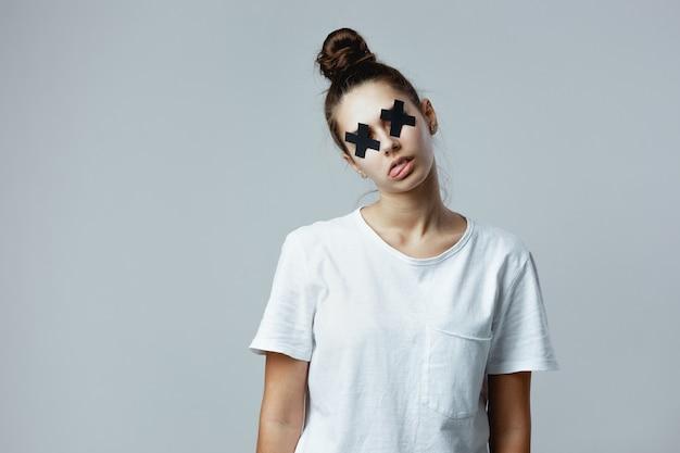 目に粘着テープの黒い十字が付いた白いtシャツを着た女の子は、スタジオの白い背景にゾンビのようにポーズをとっています。