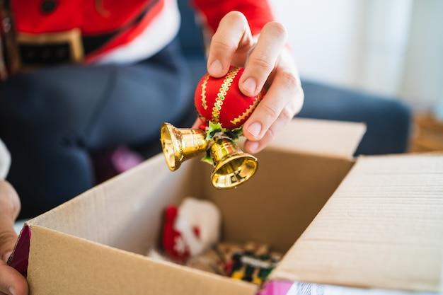 Девушка в костюме деда мороза достает из коробки рождественские украшения
