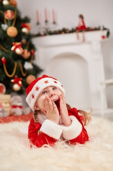 Girl dressed in santa claus lying on the floor with hands on face