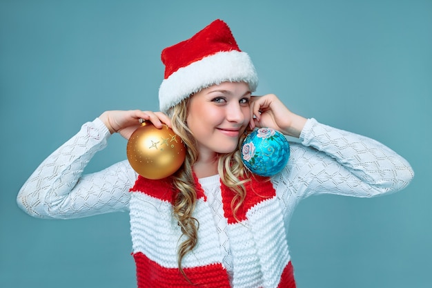 Girl dressed in santa hat  holding a christmas decoration balls on blue