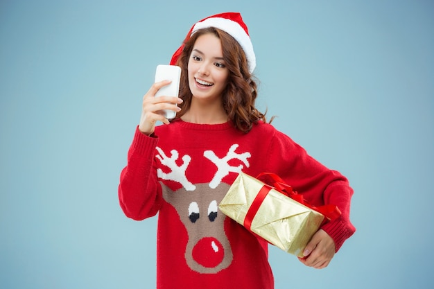 Girl dressed in santa hat with a christmas gift and phone. she is taking selfie picture. holiday concept with blue background.