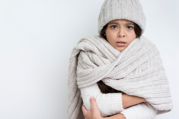 Girl dressed warmly with hands clasped at chest