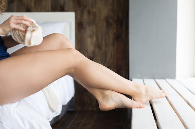 Девушка одевает гольфы, сидя на кровати в спальне. ее ноги упираются в подоконник.