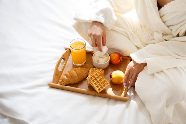 Girl  in a dressing gown eating breakfast in bed