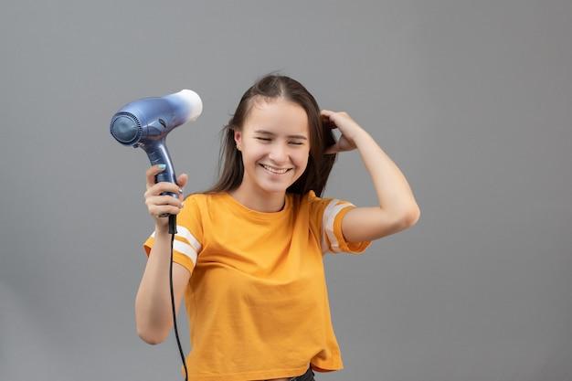 Девушка сушит волосы феном на сером фоне, развлекаясь