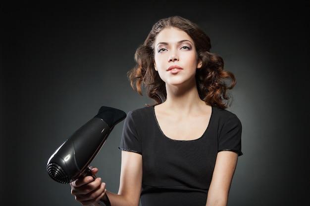 Девушка сушит длинные волосы феном на темном фоне. концептуальное фото