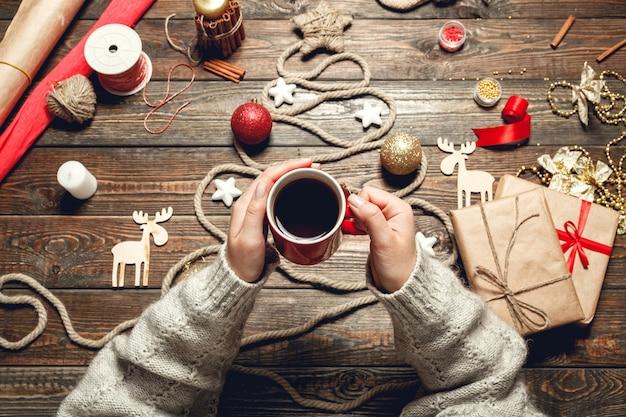 女の子はクリスマスアクセサリーと木製のテーブルで熱いお茶を飲む