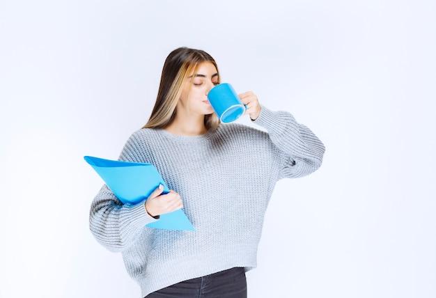 Девушка пьет чашку кофе в перерыве.