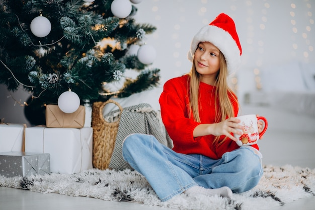 クリスマスツリーでココアを飲む女の子