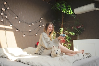 Girl drinking coffe in bed in pajamas with dog