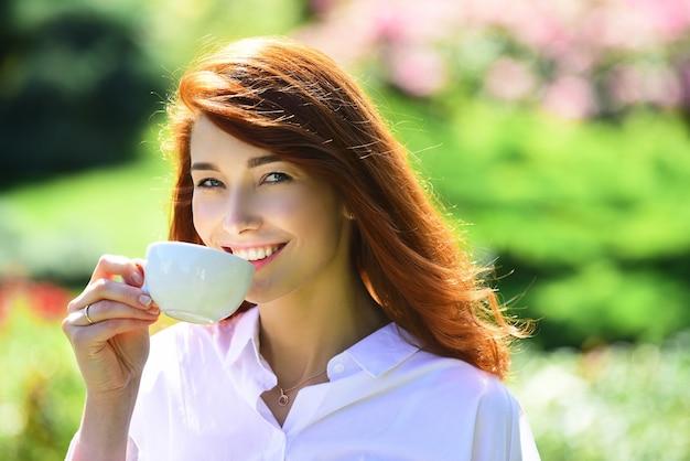 Девушка пьет кофе молодая женщина перерыв, держа чашку и пить кофе