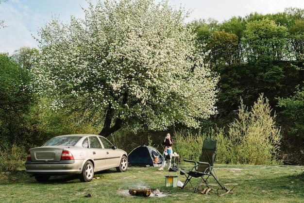 火のそばのピクニックでコーヒーを飲む女の子。自然の中でのテントでの休息と休暇。旅行の概念。幸せな家族での休暇。