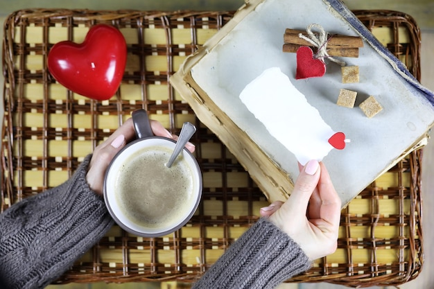 Girl drinking coffee and looking at the card valentine's day