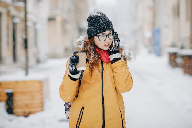 Girl drinking coffee and talking on the phone outside in winter