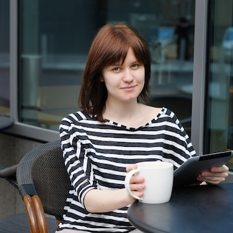 Girl drinking coffee and using tablet computer in a outdoor cafe
