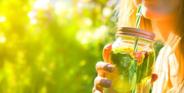 ストローの瓶で新鮮なレモネードを飲む女の子。流行に敏感な夏の飲み物。自然の中で環境にやさしい。ガラスにミントが入ったレモン、オレンジ、ベリー。