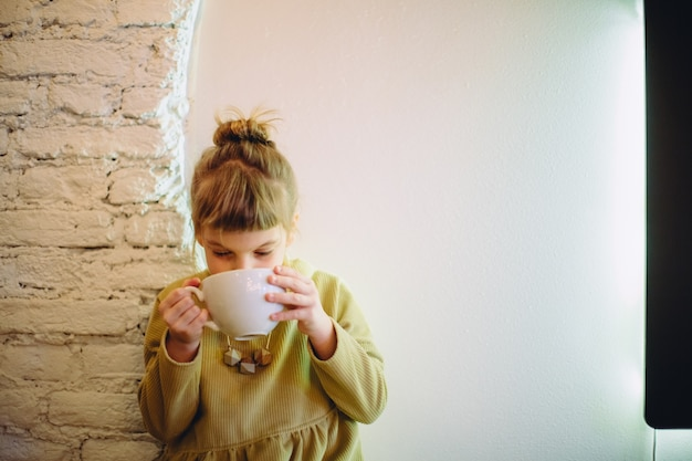 A girl drinking from a big cup