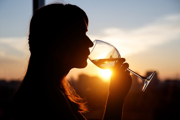 Girl drinking from a glass at sunset.