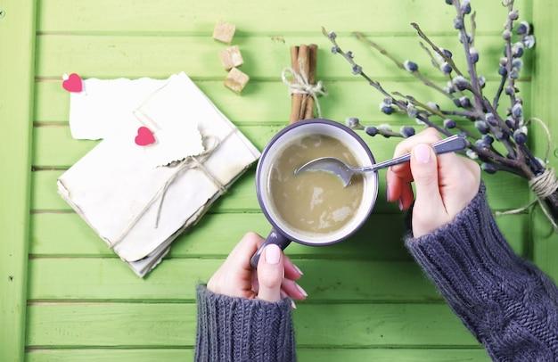 マグカップからホットコーヒーを飲み、バレンタインを提示されたように見える女の子